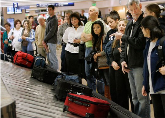 Image of an airport baggage claim carousel with people waiting for their bags.